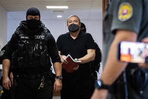 Former special prosecutor Dušan Kováčik escorted to the courtroom on September 20.
