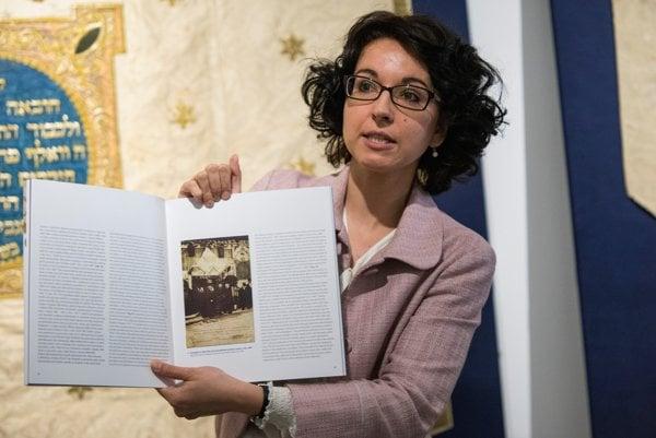 Curator Jana Švantnerová showing a historical photo in the catalogue.