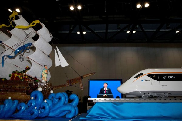 Chinese President Xi Jinping speaking at the opening of the Belt and Road Forum is displayed on a big screen near decorations depicting a modern high speed train and Chinese Admiral Zheng, who commanded expeditionary voyages across Asia and East Africa in the 15th century, in Beijing on May 14.