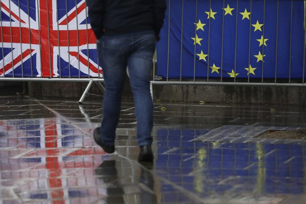 Flags tied to railings outside Parliament are reflected on a wet pavement in London, January 24, 2019.
