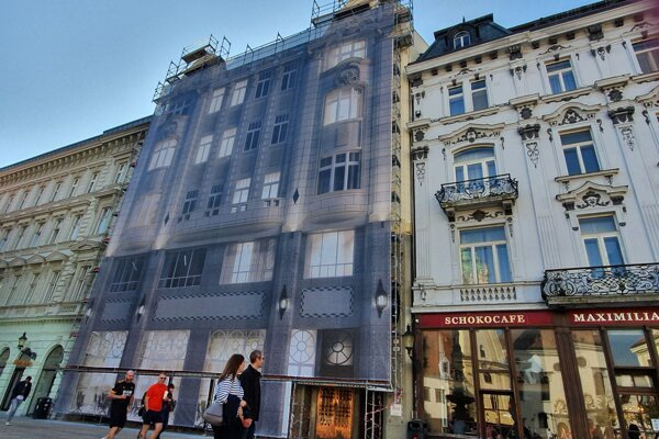 The burned facade of the secession style palace is hidden behind a textile copy of the original facade.