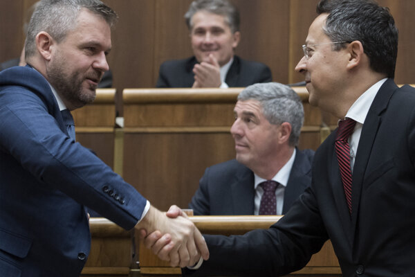 PM Peter Pellegrini and Finance Minister Laislav Kamenický shake hands after parliament passed the state budget for 2020.