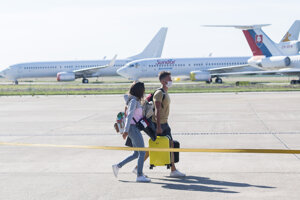 Slovak holidaymakers walk towards a Ryanair plane July 4 at M. R. Štefánik Airport in Bratislava.