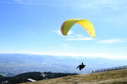 A paraglider flies over a valley from the Martinské hole mountains.