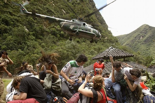 Evacuees angle for a good shot while dodging their rescue helicopter's downdraft