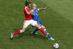 Wales's Gareth Bale, left, challenges for the ball with Slovakia's Martin Škrtel during the Euro 2016 Group B soccer match between Wales and Slovakia, at the Nouveau stadium in Bordeaux, France, Saturday, June 11, 2016.