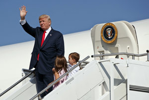 Trump waves as he walks down the steps of Air Force One with his grandchildren after arriving at Morristown Municipal Airport to begin his summer vacation at his Bedminster golf club in Morristown, N.J.
