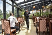 A waiter brings a meal to a customer in a Chinese restaurant in Bratislava on May 20, 2020.