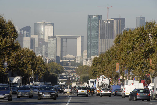 A busy Paris street, with La Défense in the background.