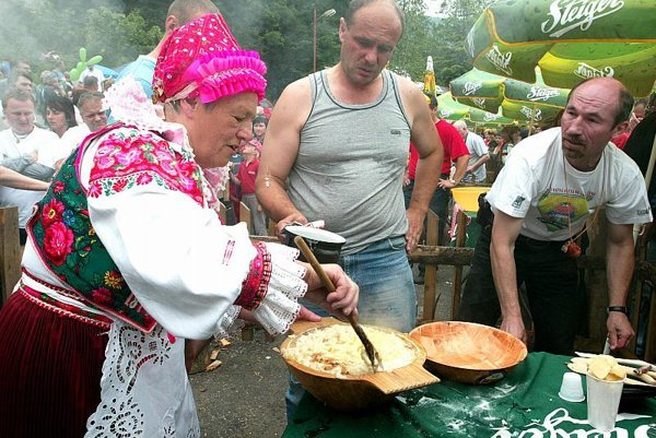 Slovaks in traditional costume enjoy halušky.