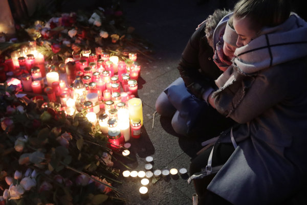 Two women mourn beside candles in Berlin, Germany, the day after a truck ran into a crowded Christmas market nearby and killed several people.