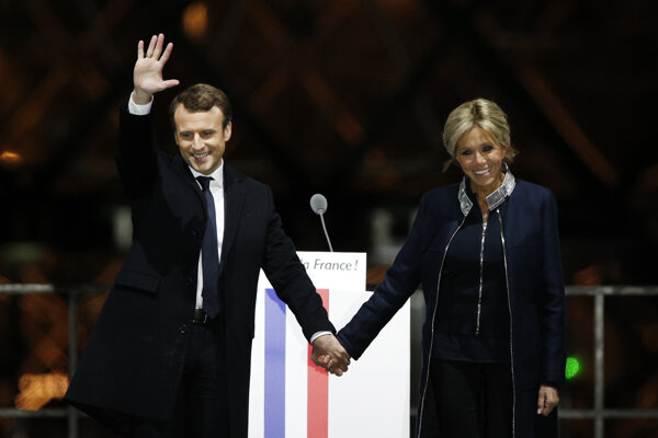 French President-elect Emmanuel Macron holds hands with his wife Brigitte during a victory celebration in Paris on May 7.