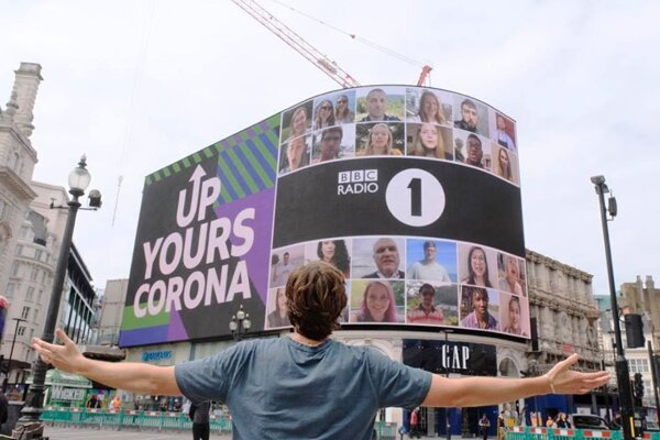 BBC Radio 1's Greg James looks at a huge billboard in London after he completes his global 'Up Yours Corona' mission on July 29, 2020.
