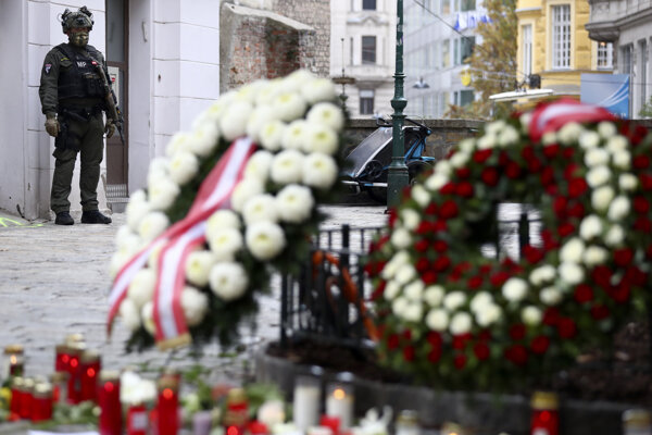 An military police officer guard at the crime scene behind wreaths and candles in Vienna, Austria, on November 4, 2020.