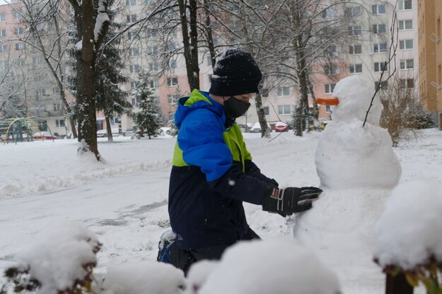 A boy builds a snowman in one of the boroughs in Žilina on January 13, 2021.