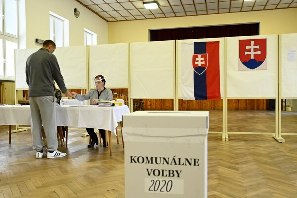 Members of the local election commission register a voter in the list of voters during the by-elections to the local government bodies on October 3, 2020 in the village of Veľká Hradná in the Trenčín Region.