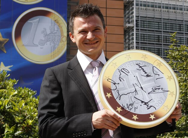 Ján Počiatek as finance minister in 2008, posing with a mock-up of a Slovak euro coin in Brussels after the final crown–euro conversion rate was confirmed.