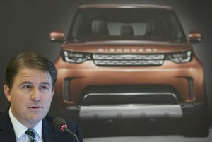 Alexander Wortberg, operations director of JLR Slovakia in front of the poester with the model Land Rover Discovery.