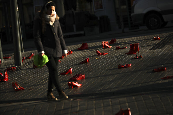 A woman walks among dozens of red painted shoes placed on the ground as a part of an installation against violence against women in Brussels.