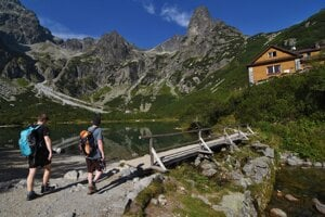 Tourists walk to a mountain hut by the Green Mountain Lake (Zelené pleso) in Belianske Tatry.