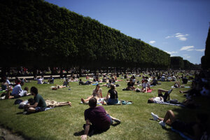 People sit in the sun on a lawn of the Jardin du Luxembourg park in Paris.