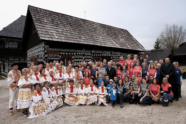 Athletes and local people pose next to buildings bearing typical Čičmany decorations.