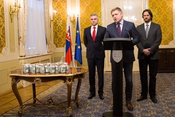 Gašpar, Fico, and Kaliňák (right to left). The one million euros that the government offers for information about the murder is displayed on the table.