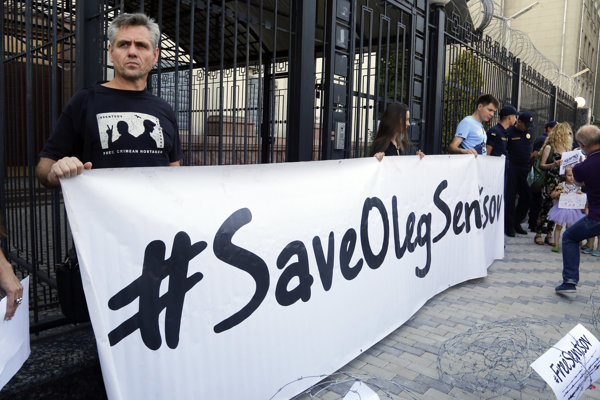 People hold posters to support Ukrainian filmmaker Oleg Sentsov, who is currently on hunger strike in a Russian jail to demand the release of the other Ukrainian hostages taken by the Kremlin, in front of the Embassy of the Russian Federation in Kiev on August 21, 2018.