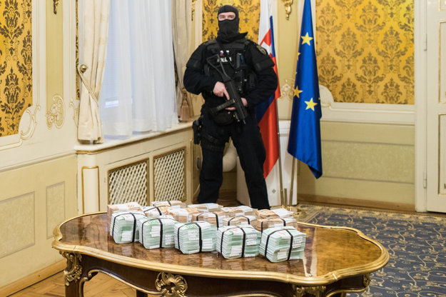 PM Robert Fico organises a press conference, standing in the government's office room next to a table with €1 million in cash on it.