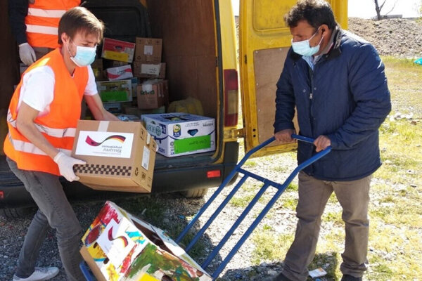 Tani with Cyriakus, an EUAV volunteer, distributing food supplies during COVID-19 pandemic.