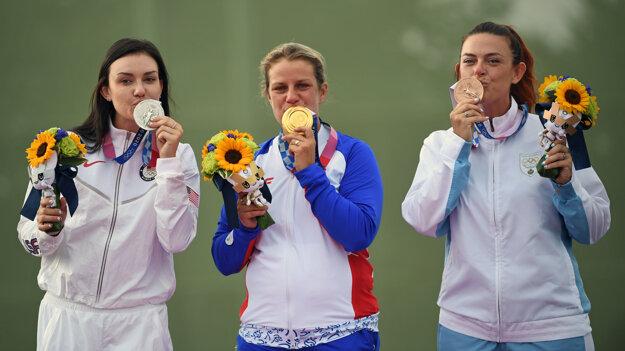 Slovak sports shooter Zuzana Rehák Štefečeková (centre) wins a gold medal in Tokyo.