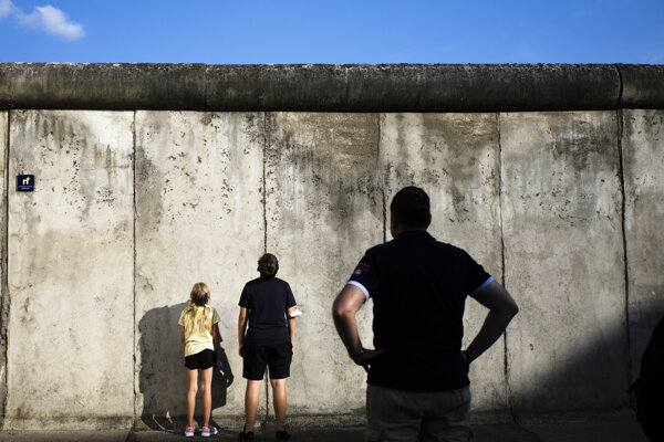 Visitors stand in front of the remains of the Berlin Wall on a street in Berlin on August 12, 2021.