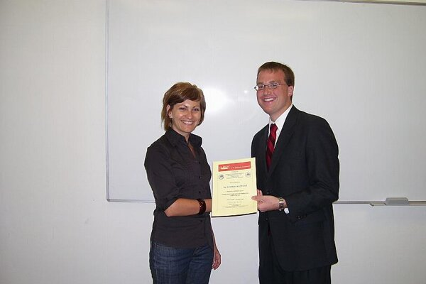 Sean Deskins awarding a certificate to one of his students.