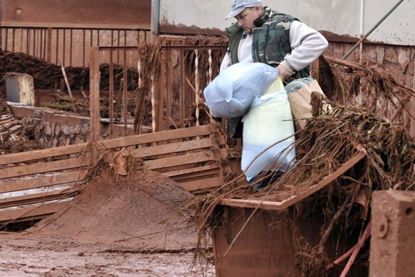 A man retrieves belongings from his home flooded by toxic mud in Kolontar.