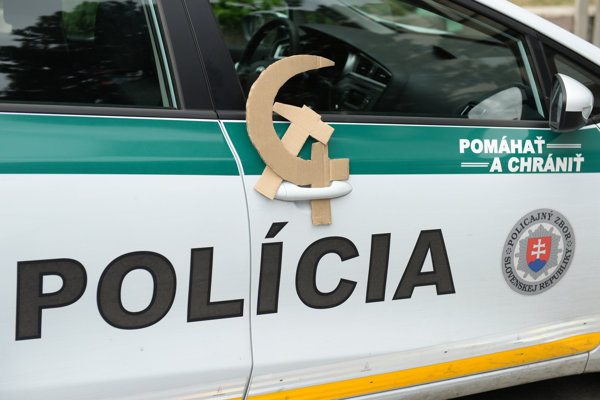 Protesting citizens attached hammer and sickle to a police car.