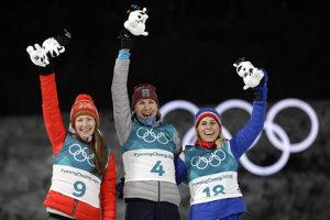 Silver medalist Darya Domracheva (l), of Belarus, gold medalist Anastasiya Kuzmina, of Slovakia, and bronze medalist Tiril Eckhoff (r), of Norway, celebrate during the venue ceremony at the women's 12.5-kilometer mass start biathlon.