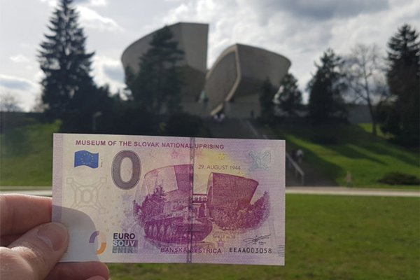 The souvenir banknote with the SNP Monument in the background.