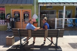 Two women sit on a bench opposite an ice-cream parlour in Carolina Beach, North Carolina, USA.