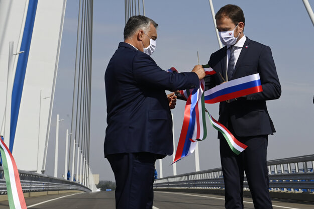 Hungarian PM Viktor Orban (left) and Slovak PM Igor Matovič exchange the ribbons they've just cut during the inauguration ceremony of a new bridge across the Danube River connecting the two countries in Komárom, Hungary.