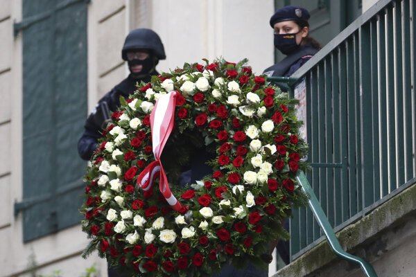 A man carries a wreath as he walks past police officers in Vienna, Austria, Tuesday, Nov. 3, 2020.