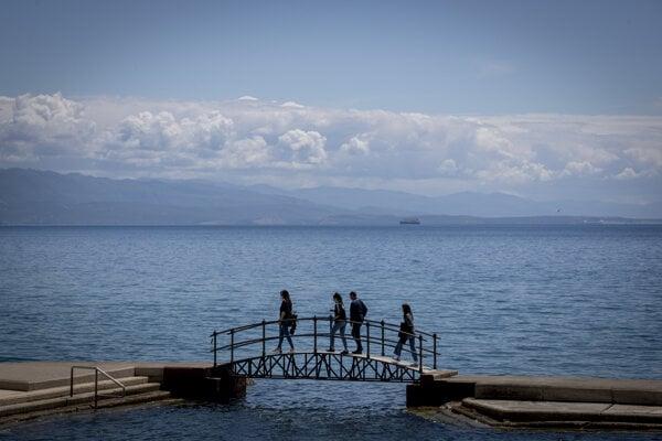 A group of tourists walk across a bridge on the seafront in Opatija, Croatia.
