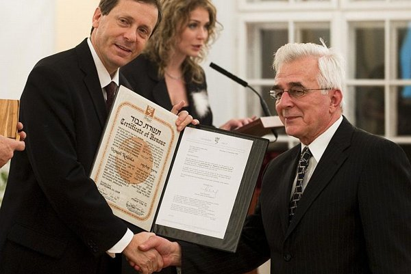 Ivan Kolenka (right) accepts a certificate on behalf of his uncle Vojtech from Isaak Herzog.
