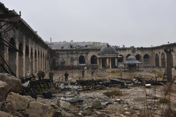 Syrian troops and pro-government gunmen marching walk inside the destroyed Grand Umayyad mosque in the old city of Aleppo, Syria.