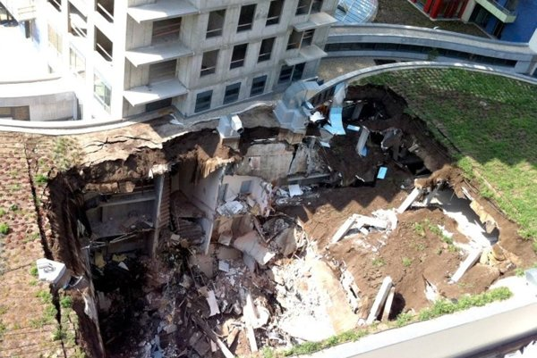The collapsed building left a crater full of construction debris.