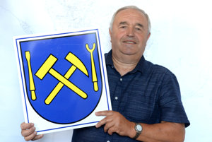 Mayor Stanislav Rusnák shows the miners's logo.