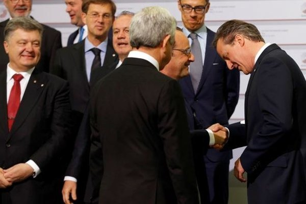 British PM David Cameron (R) shakes hands with French President Francois Hollande at Eastern Partnership summit. Front row left is Ukrainian President Petro Poroshenko, next to him Slovak president Kiska.