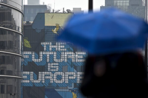 A man walks with an umbrella outside EU headquarters in Brussels.