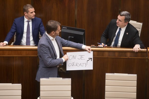 "OĽaNO chair Igor Matovič (centre) is holding a banner saying ""He is drunk"", referring to Speaker of Parliament Andrej Danko (r)."