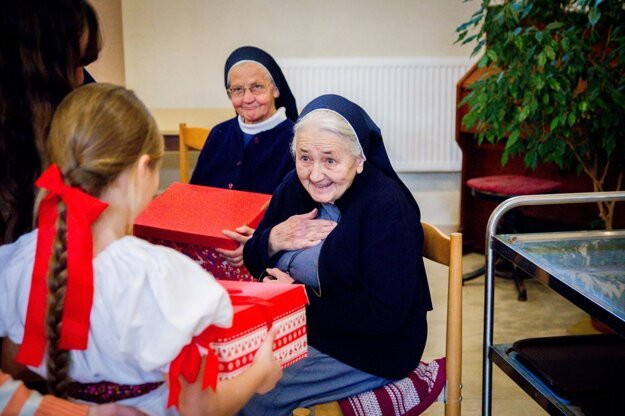 Older people receive Christmas presents from children.