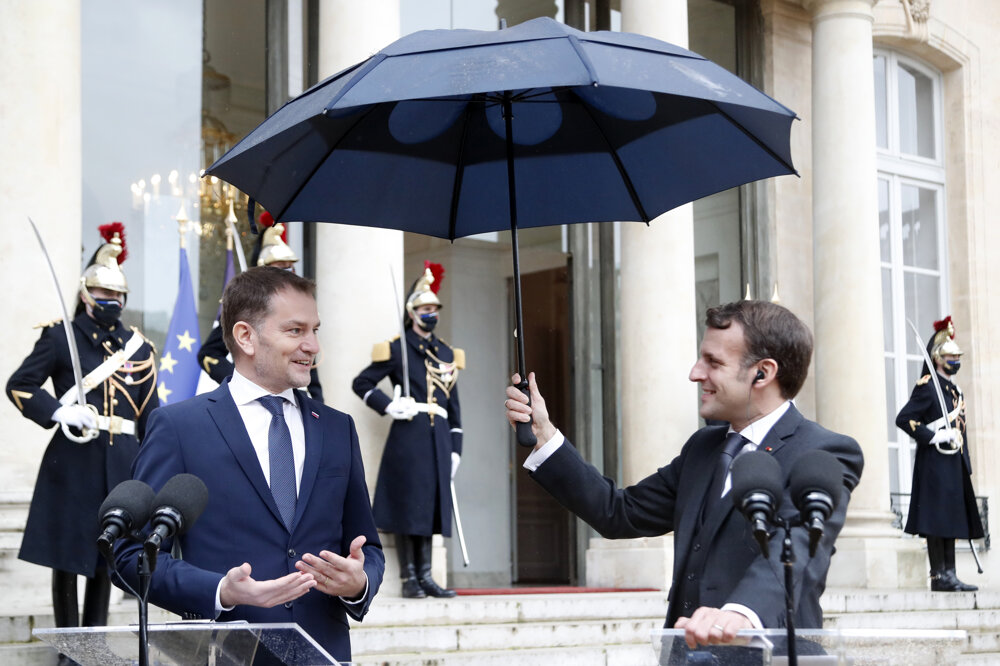 French President Emmanuel Macron holds an umbrella as Slovakia's PM Igor Matovič speaks to the medias before a business lunch at Elysee Palace on February 3, 2021 in Paris.